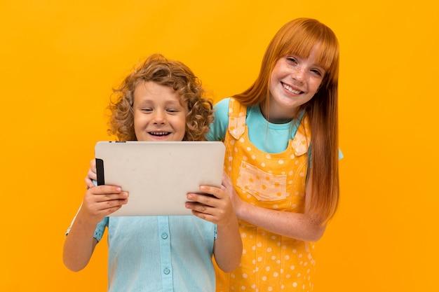 Twee gelukkige broer en zus met zomerhoeden zijn verrast om de tablet op een gele achtergrond te bekijken