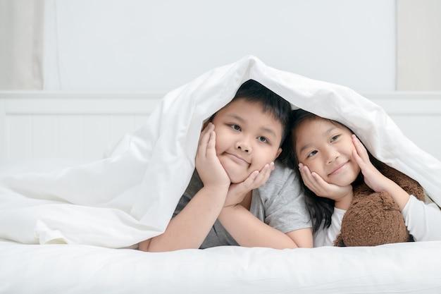 Twee gelukkige broer of zus kinderen liggend onder deken,