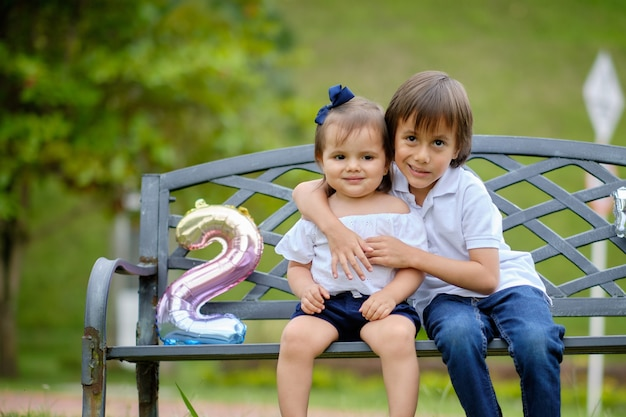 Twee gelukkige broers die als openluchtstoel zitten. broer knuffelen zijn zus.