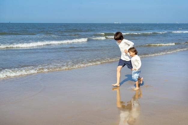 Twee gelukkige broers hand in hand rennen langs de kust aan de noordzee. jongens die weekend doorbrengen aan de kust in belgië, knokke. broers en zussen vriendschap concept.