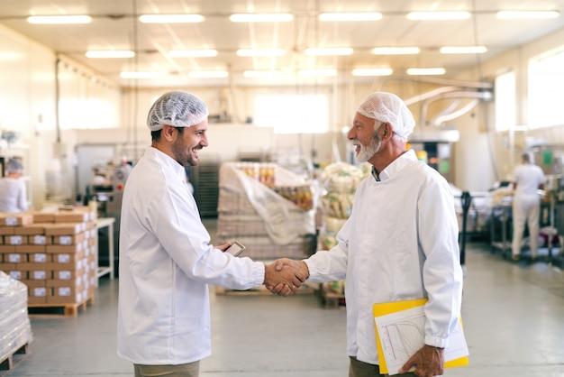 Twee gelukkige collega's handen schudden terwijl ze in de voedselfabriek staan.