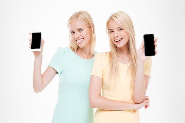 Twee gelukkige dames die hun telefoons tonen. ge oleerd over witte muur