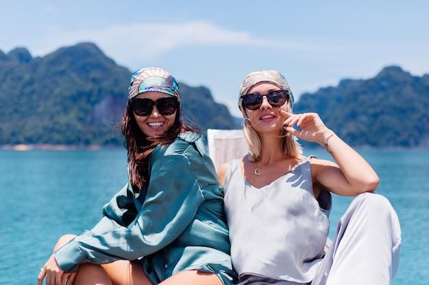 Twee gelukkige de toeristenvrienden van de vrouwenblogger in zijden kostuum en sjaal en zonnebril op vakantiereis rond thailand op aziatische boot, nationaal park khao sok.