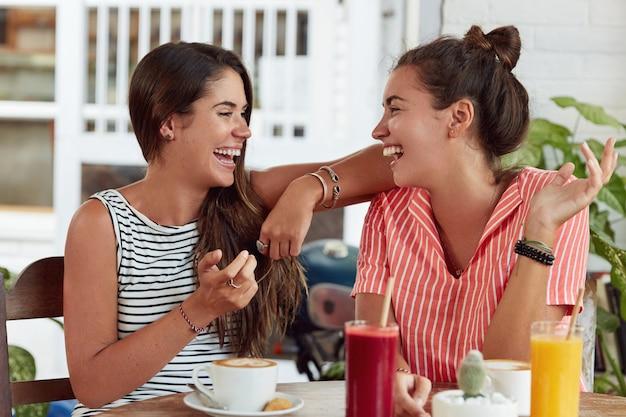 Twee gelukkige dolgelukkige vrouwen zitten op terras, drinken cocktails, cappuccino, vertellen grappige verhalen aan elkaar