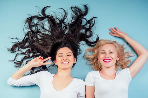 Twee gelukkige en aantrekkelijke vriendinnen brunette en blonde vrouwen liggen op de vloer in de studio op een blauwe achtergrond. concept van vriendschap voor altijd