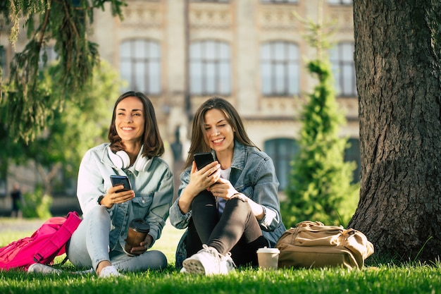 Twee gelukkige en opgewonden student vriendinnen in casual denim kleding zijn ontspannen in college park met smartphones en hebben plezier.