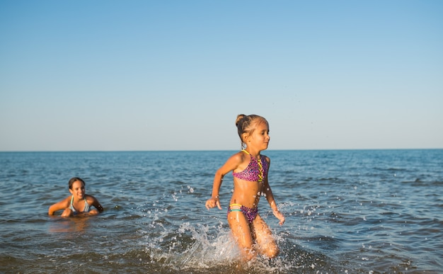 Twee gelukkige en positieve meisjeszusjes rennen langs de golven van de zee tijdens hun vakantie op een zonnige hete zomerdag