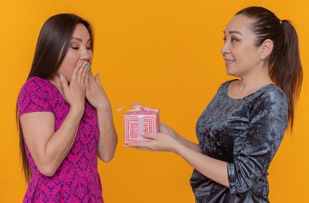 Twee gelukkige en vrolijke aziatische vrouwen die de dagvrouw van internationale vrouwen vieren die een cadeau geven aan haar verraste beste vriend die zich over oranje muur bevindt