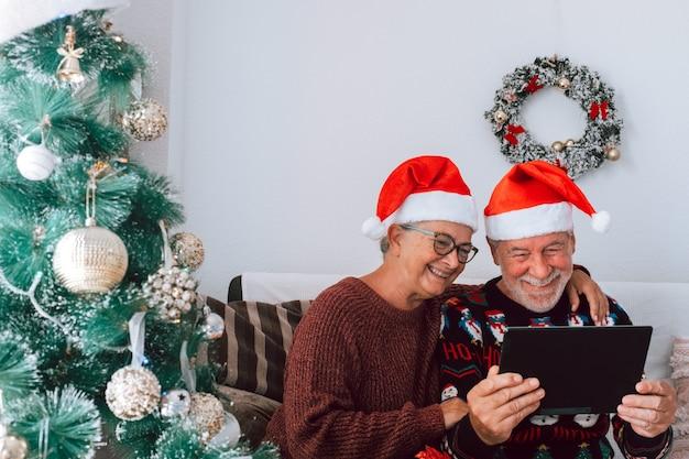 Twee gelukkige en vrolijke senioren die op de bank zitten en samen dezelfde tablet of hetzelfde technologieapparaat gebruiken op kerstdag - volwassen mensen die plezier hebben