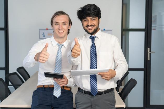 Twee gelukkige financiële analisten die rapporten goedkeuren.