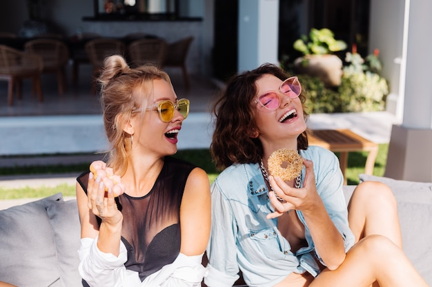 Twee gelukkige fit vrouw in roze en gele zonnebril lachend plezier lachen met donuts, buiten