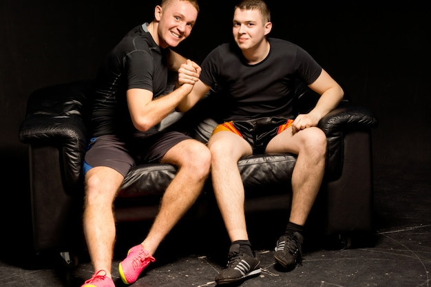 Twee gelukkige, fitte jonge mannen die een vriendelijke armworsteling hebben terwijl ze samen zitten