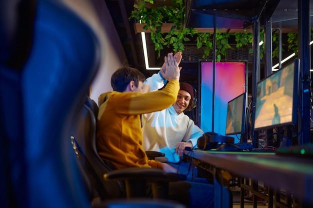 Twee gelukkige gamers in headsets spelen in gameclub