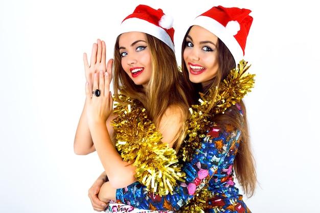 Twee gelukkige gekke beste vriendenmeisjes klaar voor het vieren van nieuwjaarsfeest
