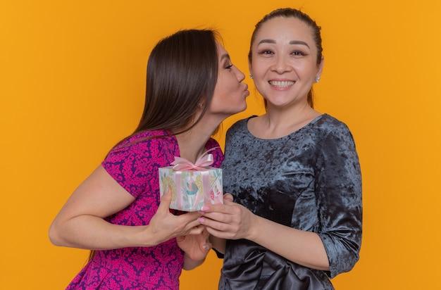Twee gelukkige glimlachende aziatische vrouwen die de dag van internationale vrouwendag vieren gelukkige vrouw die haar beste vriend kust die een cadeau ontvangt dat zich over oranje muur bevindt