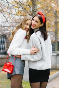 Twee gelukkige glimlachende vrienden omhelzen en lopen door de herfst