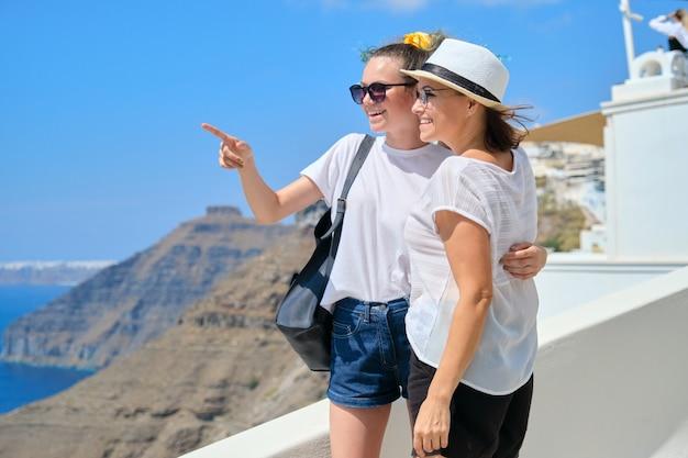 Twee gelukkige glimlachende vrouwen, moeder en tienerdochter die samen reizen, luxe reizen op cruiseschip naar het beroemde griekse eiland santorini