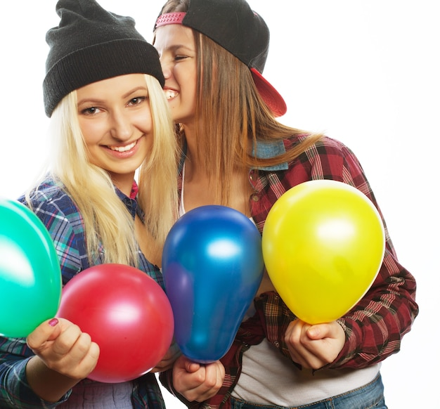 Twee gelukkige hipster meisjes glimlachen en houden gekleurde ballonnen op witte achtergrond