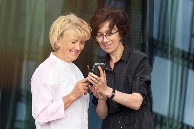 Twee gelukkige hogere vrouwen die smartphone bekijken en lachen
