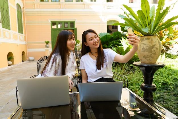 Twee gelukkige jonge aziatische tienervrouwen met laptop die selfie samen bij de koffiewinkel nemen