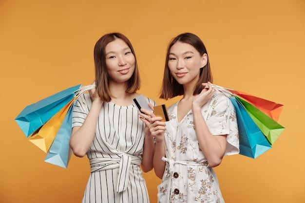 Twee gelukkige jonge aziatische vrouwelijke tweelingconsumenten met papieren zakken en creditcards die voor de camera staan tegen een gele achtergrond