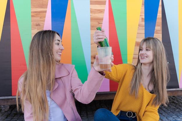 Twee gelukkige jonge blanke vrouwen toast met drankje op de veelkleurige muur van een stadsbar
