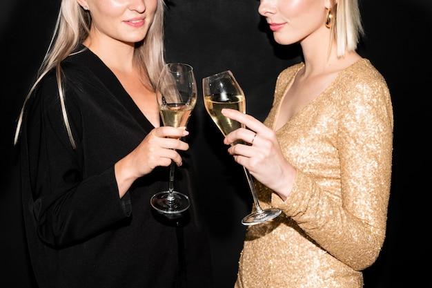 Twee gelukkige jonge elegante vrouwen rammelende met fluiten champagne tijdens het vieren van de verjaardag van een van hen op feestje in de nachtclub