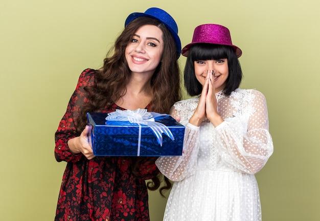 Twee gelukkige jonge feestvrouwen met een feestmuts, een met een cadeaupakket, een ander meisje dat de handen bij elkaar houdt voor de mond, beide kijkend naar de voorkant geïsoleerd op de olijfgroene muur