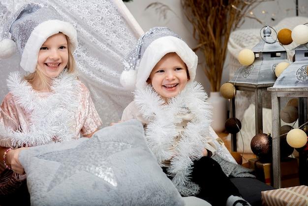 Twee gelukkige jonge geitjes - meisje en jongen die een kerstmutsen dragen die thuis onder de vakantiedecoratie zitten