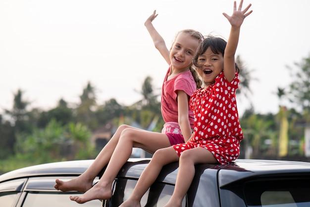Twee gelukkige jonge jongen zittend op de top van de auto en spelen
