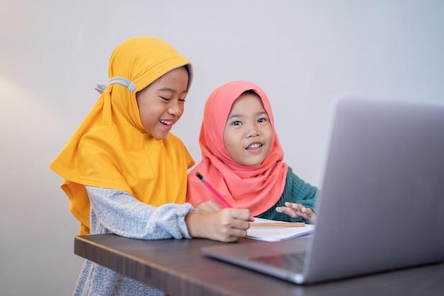 Twee gelukkige jonge kinderen studeren samen thuis met behulp van laptop