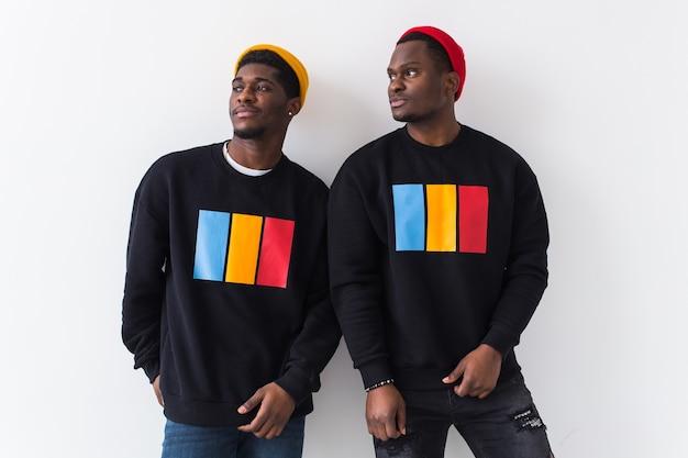 Twee gelukkige jonge mannen in zwarte stijlvolle sweatshirts