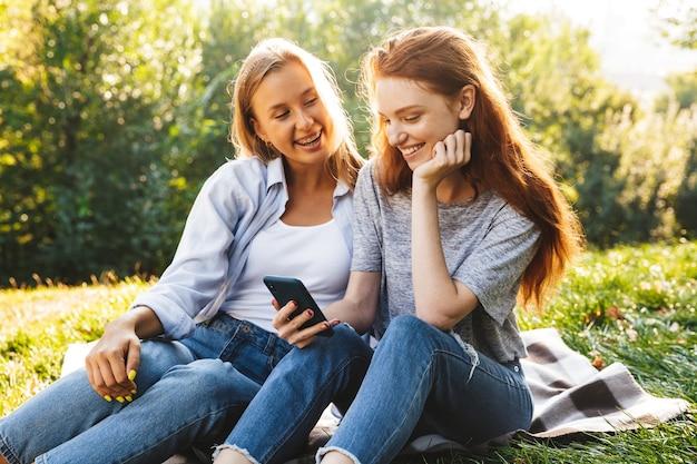 Twee gelukkige jonge meisjes die plezier hebben in het park