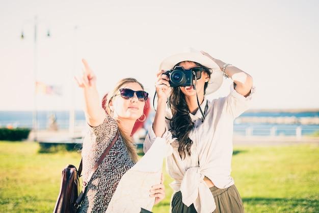 Twee gelukkige jonge meisjes toeristen met rugzakken, toeristische kaart en camera.
