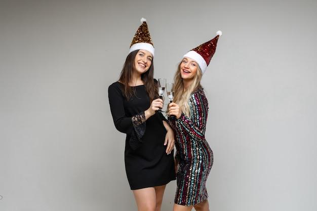 Twee gelukkige jonge meisjesvrienden die in santahoeden nieuwjaar en kerstmis vieren