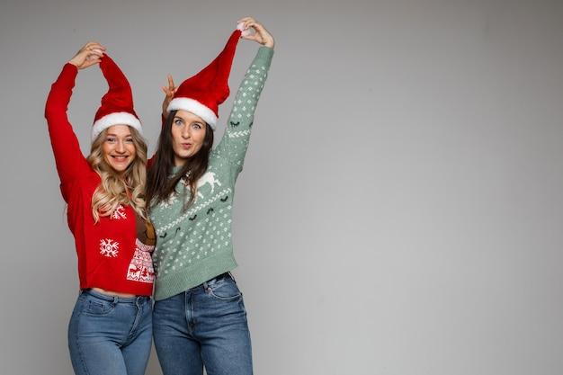 Twee gelukkige jonge meisjesvrienden die met kerstmutsen op grijze achtergrond voor de gek houden met kopieerruimte voor kerstmis nieuwjaarsadvertentie