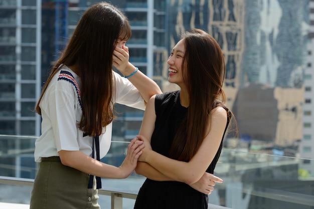 Twee gelukkige jonge mooie aziatische tienervrouwen die samen tegen mening van de stad lachen
