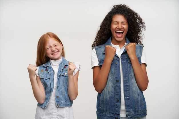 Twee gelukkige jonge mooie meisjes in vrijetijdskleding die vreugdevol hun vuisten balanceren en de ogen gesloten houden, in een hoge geest zijn en breed glimlachen terwijl ze op wit staan