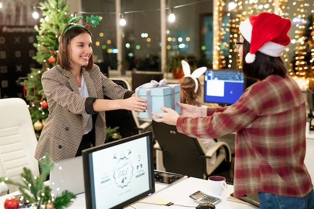 Twee gelukkige jonge ondernemers geven elkaar cadeautjes via computermonitor op eerste kerstdag in kantoor