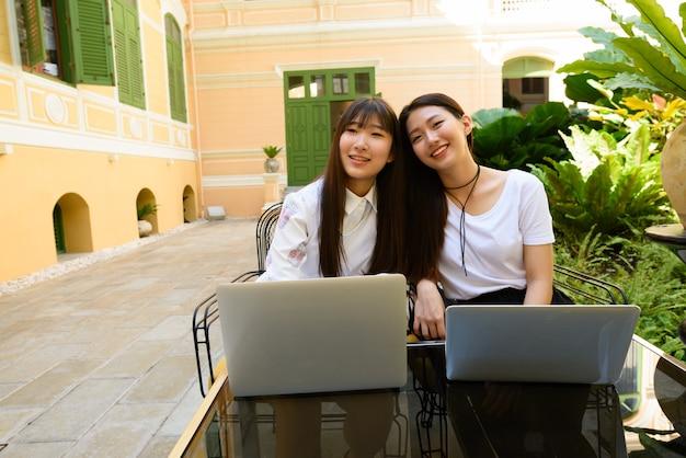 Twee gelukkige jonge tiener aziatische vrouwen die laptop samen met behulp van bij de koffiewinkel