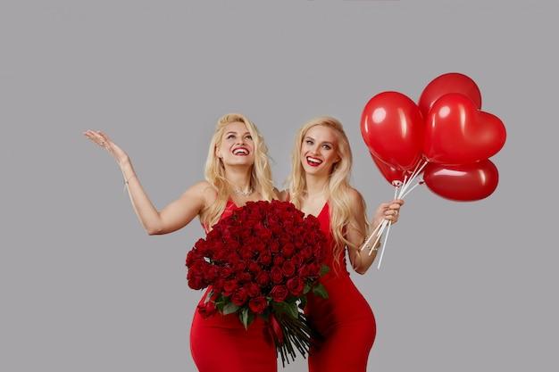 Twee gelukkige jonge tweeling met een groot boeket van rode rozen en een rode hartvormige ballonnen.