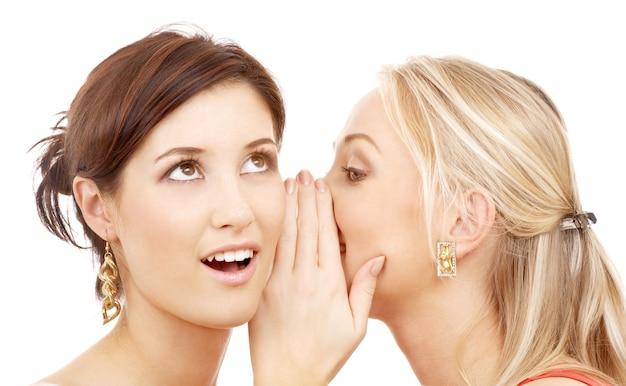 Twee gelukkige jonge vriendinnen praten over wit