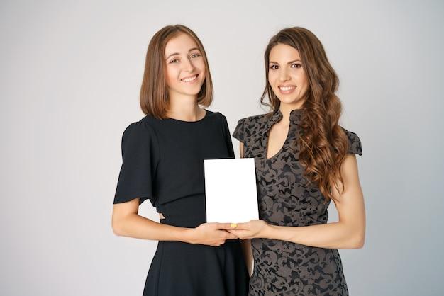 Twee gelukkige jonge vrouwen die een model op de achtergrond houden