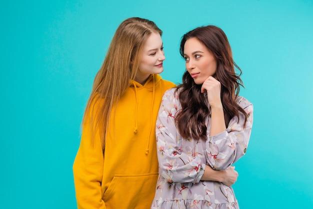 Twee gelukkige jonge vrouwen die elkaar geïsoleerd houden