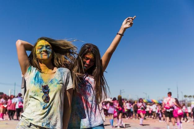 Twee gelukkige jonge vrouwen die en in het holifestival genieten van dansen