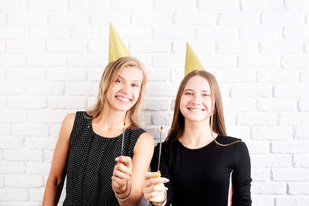 Twee gelukkige jonge vrouwen die in verjaardagshoeden sterretjes houden die verjaardag vieren, die gouden verjaardagshoeden dragen over witte bakstenen muurachtergrond