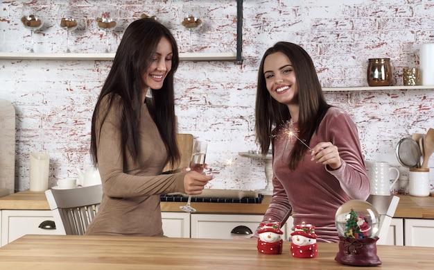 Twee gelukkige jonge vrouwen die nieuw jaar vieren met wonderkaarsen