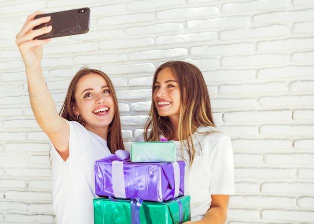 Twee gelukkige jonge vrouwen die selfie op smartphone nemen