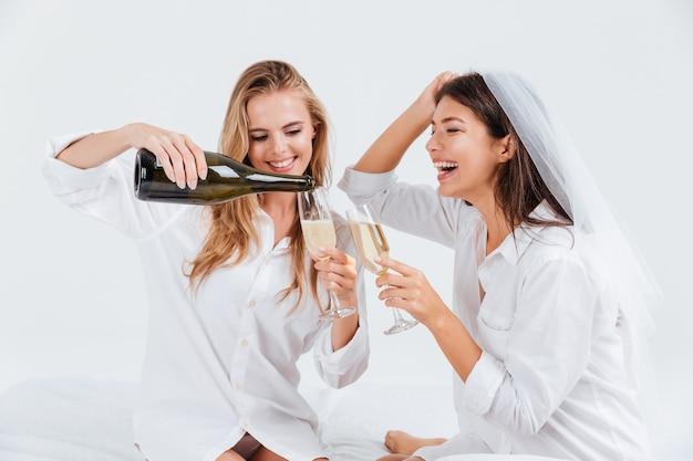 Twee gelukkige jonge vrouwen hebben een verlovingsfeest met een fles champagne