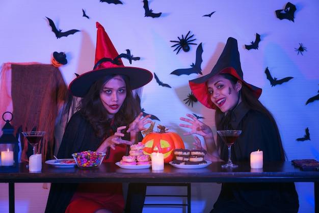 Twee gelukkige jonge vrouwen in de kostuums van zwarte hekshalloween op partij met pompoen en cocktails